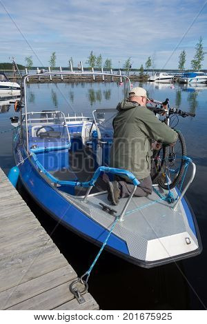 TAIPALSAARI, FINLAND - JULY 2: Unidentified fishing guide ties two touring bikes securely to a fishing boat in marina by the lake Saimaa Finland for crossing to the other side of the lake from Taipalsaari July 2, 2015.