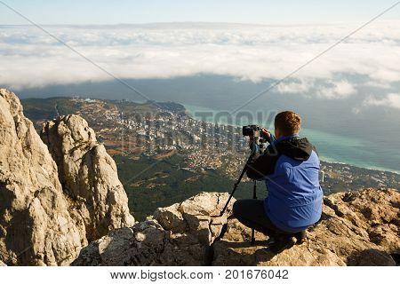 Man sitting with a tripod and photo camera on a high mountain peak above clouds, city and sea. Pro photographer adjusting dslr settings on rocky summit. Ai Petri, Yalta, Crimea.