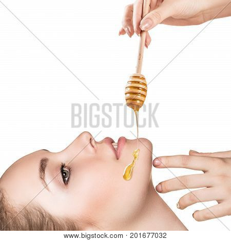 Honey flows down on woman's face from spoon. Honey therapy concept. Isolated on white background.