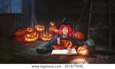 Halloween. little witch child conjures with book of spells magic wand and pumpkins