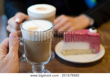 Two latte coffees with foam and cake restaurant woman and man