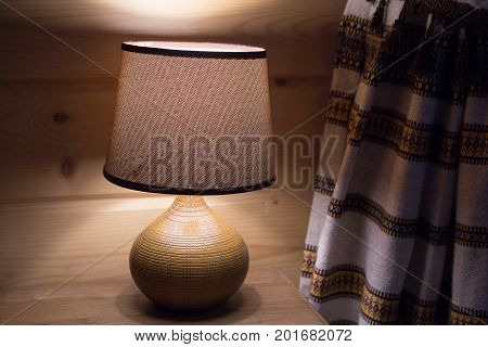 Warm lampshade of a yellow lamp in a retro interior