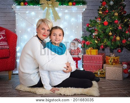 Portrait of a happy mother and her cute little daughter in front of the Christmas tree