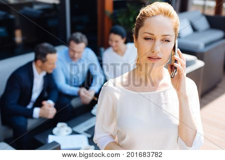 Phone call. Attractive nice pleasant businesswoman standing in the restaurant and talking on the phone while discussing work issues