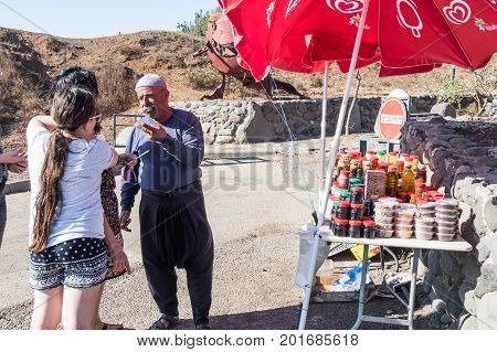 Golan Heights Israel August 27 2017 : The seller - druz trades with buyers up his store with canned sweets in the parking lot on Mount Bental. on the Golan Heights in Israel.