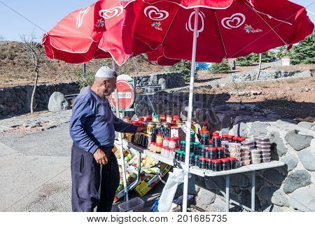 Golan Heights Israel August 27 2017 : The seller - druz stands near his shop with canned sweets in the parking lot on Mount Bental. on the Golan Heights in Israel.