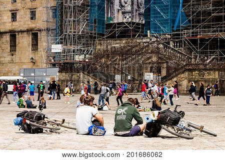 SANTIAGO DE COMPOSTELA, SPAIN. AGUST 9, 2017. Two pilgrims resting in front of the Santiago's Cathedral after the long way to the holy city.