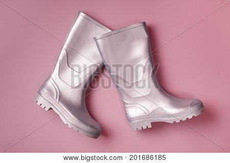 Autumn creative background: stylish silver marching rain boots on pink background. Top view. Flat lay.