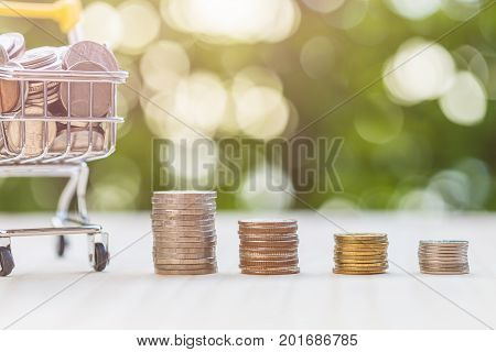 Hand Putting Coins In Stack On Wooden Plank. Savings Concept.