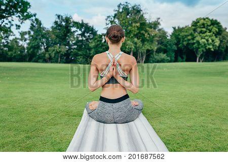 Woman Meditating On Green Lawn
