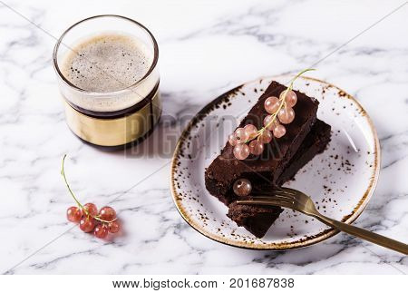 Chocolate flourless brownie cake with berries red currant and cup of coffee on a grey marble table. Healthy breakfast. Selective focus