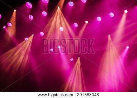 Lighting equipment on the stage of the theatre during the performance. The light rays from the spotlight through the smoke. Yellow and purple rays.