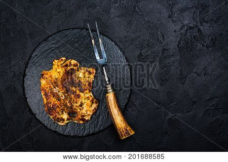 Chicken steak, fork and knife on slate board. Dark stone background. Copy space