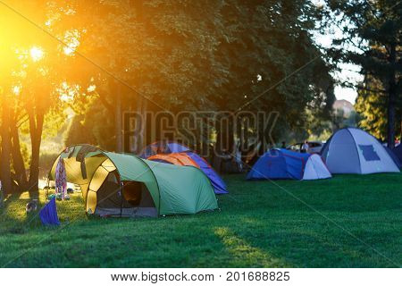 Photo of tent camp in summer park at afternoon. Lensflare effect