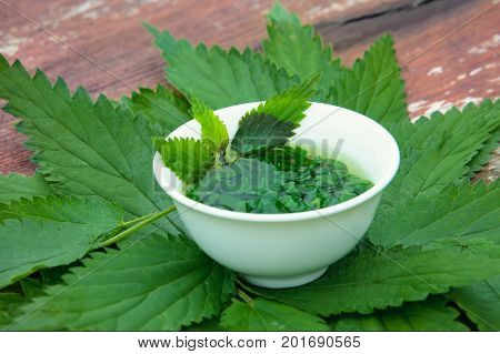 Herbs tea from leaves of a nettle on a wooden surface. Herbal Medicine.
