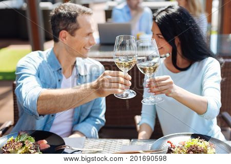 Our anniversary. Selective focus of glasses with wine being in hands of nice happy delighted couple while celebrating their anniversary