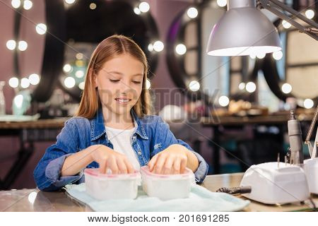Thorough preparation. Adorable teenage girl sitting at the table and preparing her nails for manicure by soaking them in finger bowls