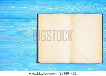 Old Black Open Book On Wooden Plank Background. Blank Empty Page For Design