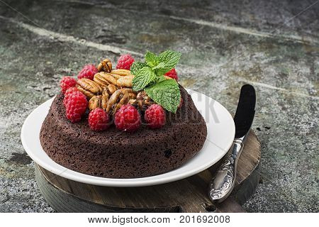 Homemade chocolate crazy cake with pecans, juicy raspberries, mint on a gray background with a vintage Melchior knife for filing. Top View