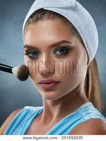 Portrait of woman wearing in bandage on head, touching face by ankle and drawing blush for herself. Female making makeup, looking at camera. Beauty, cosmetics and care concept.