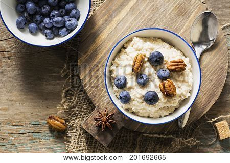 Healthy breakfast: milk porridge from oat bran on skimmed milk with honey, juicy blueberries, pecans on a simple wooden background with a spoon and a jar of honey. Top View