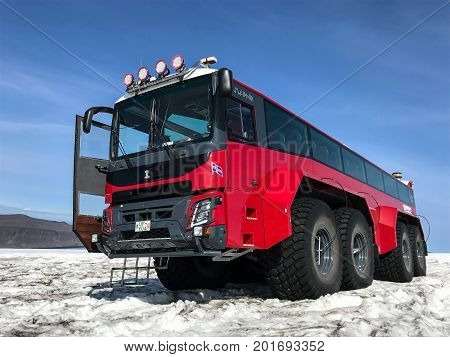 Husafell Iceland August 22 2017: Red specialty vehicle for driving on the snow stands on the surface of Langjokull glacier. This is a part of