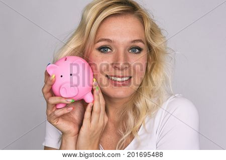 Smiling Girl With Freckles Holds A Piggy Bank.
