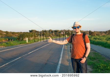 Man with Backpacks and Guitar in casual Travel Clothes walking along road , Road hitch-hiking. Traveler standing at the highway hitching