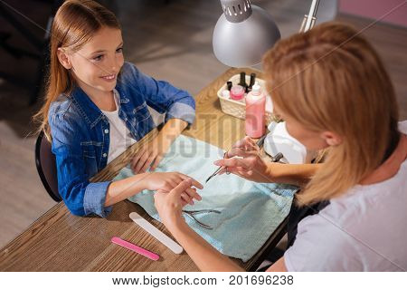 Gentle nail care. Top view of a pleasant young manicurist cutting the nails of her petite teenage client with scissors while the girl smiling at her
