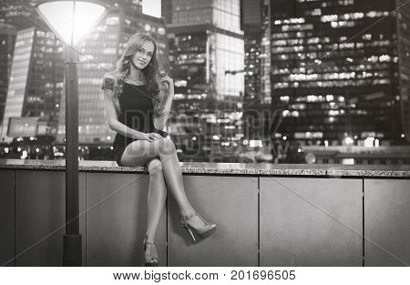 Beautiful Woman Sitting Over View On Night City Lights