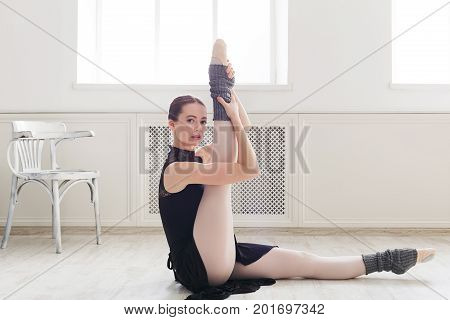 Beautiful graceful ballerina in black leotard practice leg stretching in class room background posing on camera. Ballet class training, copy space