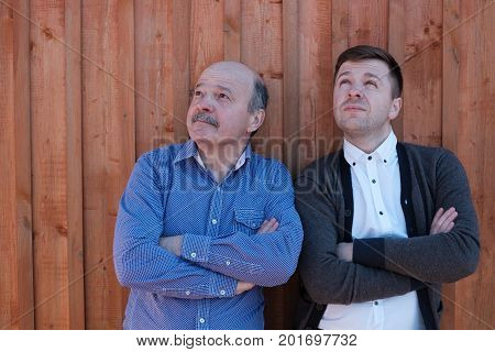 The father and the adult son are standing by the wooden wall and looking thoughtfully upward. They crossed their arms at the chest. concept of distrust and misunderstanding in family