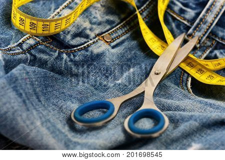 Scissors On Jeans As Making Clothes And Design Concept