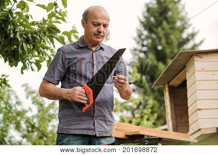 Mature man with mustache holding a saw in hand. Sawing logs, harvesting firewood for the winter