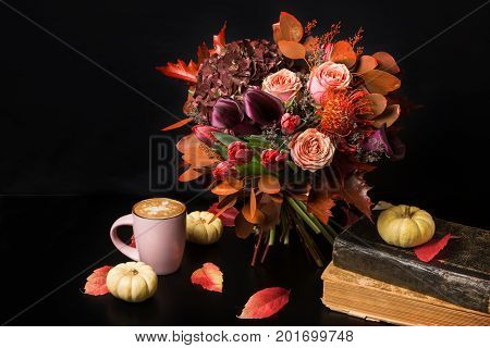 Colorful fall bouquet on black background. Autumn composition with hot cappuccino, books, roses, tulips, dry leaves and herbs. Seasonal holidays, flower shop and florist design concept, copy space