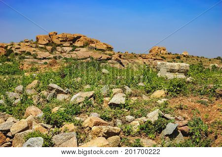 Tourist Indian landmark, Ancient ruins in Hampi. Beautiful nature scenery with bright blue sky and strange landscape with large rocks, Hampi, India