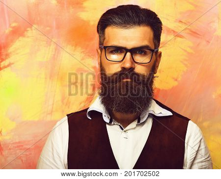 Bearded man long beard. Brutal caucasian unshaven serious hipster with glasses and moustache wearing white shirt suede waistcoat on colorful studio background