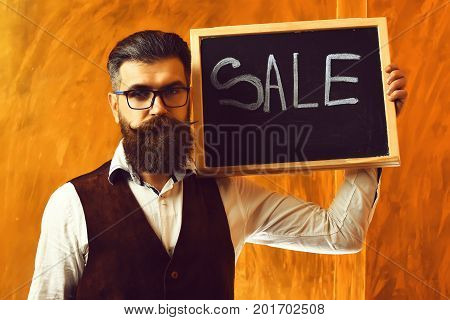 Bearded man long beard. Brutal caucasian unshaven serious hipster with glasses and moustache holding sale inscription on blackboard wearing white shirt suede waistcoat on brown studio background