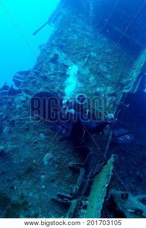 Scuba diver is exploring shipwreck, blue background.