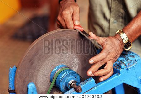 Man grinding knife on grinding wheel disk