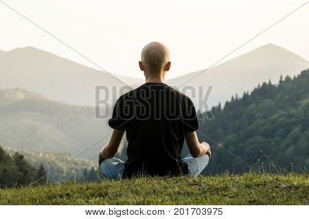 Skinny male person doing yoga sits in lotus position top of the hill in ukrainian carpathian mountains. Young man meditating in mountains at sunset