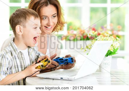 Mother and son playing computer game on laptop together