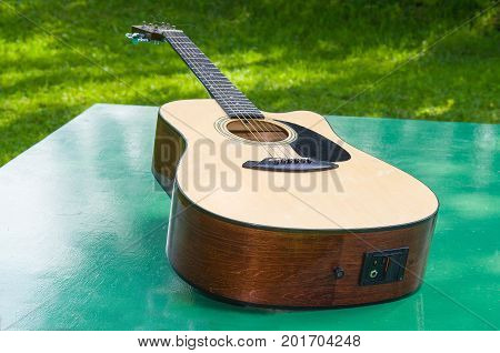 On the table in the courtyard lies acoustic six-string guitar.