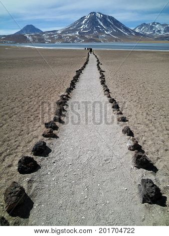 A path and some people walking toward the lagoon, in Atacama Desert, Chile