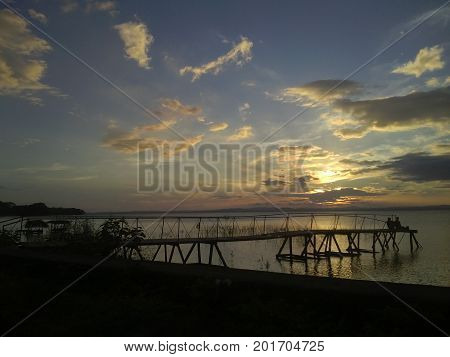 A couple, seated in a pier, watching a Beautiful Sunset at Isla Ometepe  - Ometep Island - Nicaragua