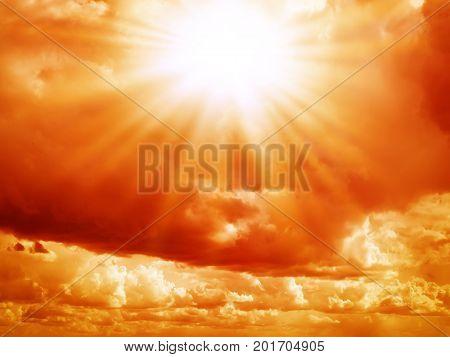 Bright sun in the red sky with cumulus clouds