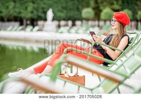 Young stylish woman in red cap and pants sitting with phone on the famous green chairs in Tuileries garden in Paris