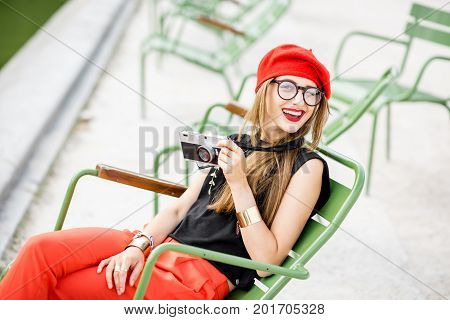 Young stylish woman tourist in red cap and pants sitting with photocamera on the famous green chairs in Tuileries garden in Paris