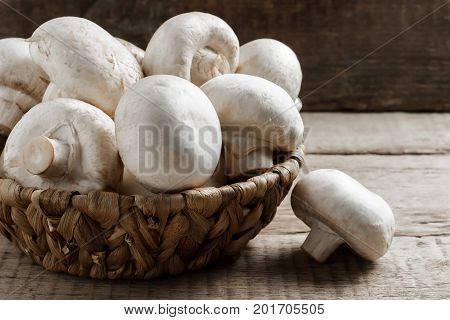 Mushrooms Champignons In A Wicker Basket On A Wooden Background