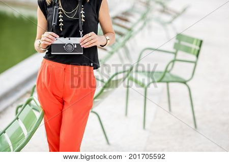 Young stylish woman tourist standing with photocamera near the famous green chairs in Tuileries garden in Paris